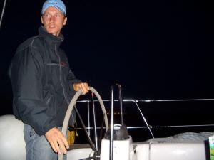 Skipper Steffen Lelewel am Steuer einer Segelyacht bei Nacht